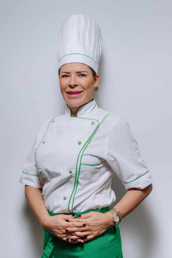 Studio portrait of a beautiful woman chef in uniform. A smiling woman cook in a cap and uniform on a gray background. stock image