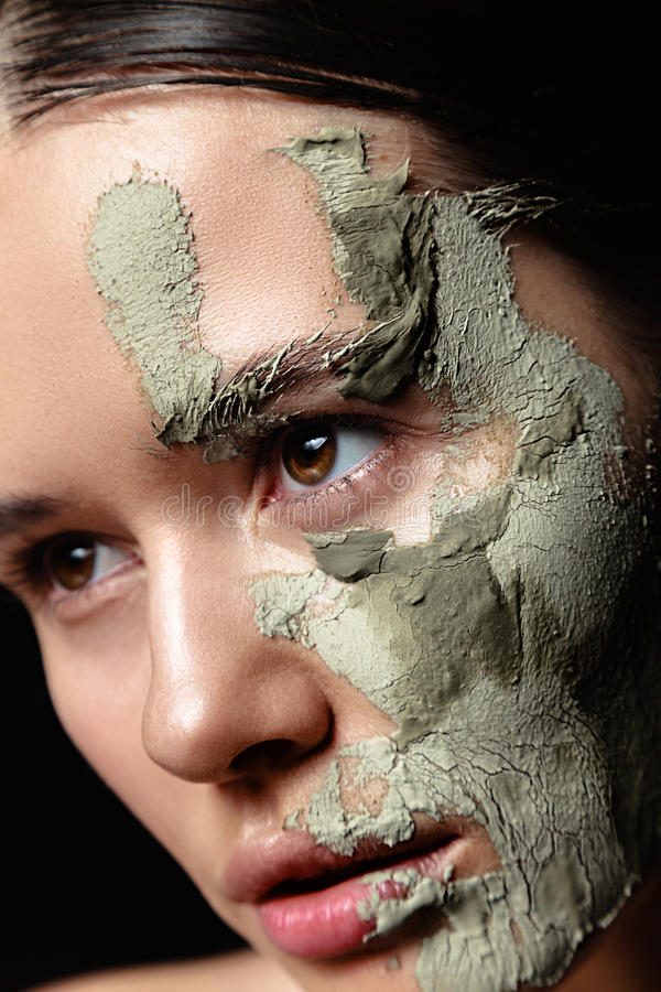 Studio portrait of beautiful woman with mud facial mask on black. Background stock image