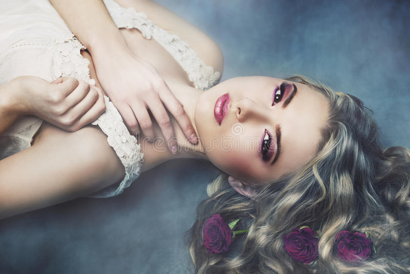 Studio portrait of beautiful woman with roses in the smoke royalty free stock image