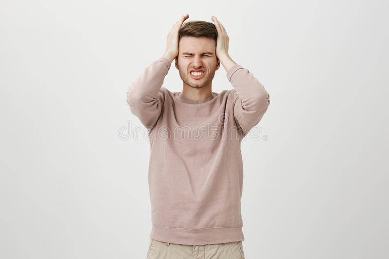 Studio portrait of beautiful young guy having terrible headache, holding hands on head and feeling pain, standing. Against gray background. Man got unexpected royalty free stock image