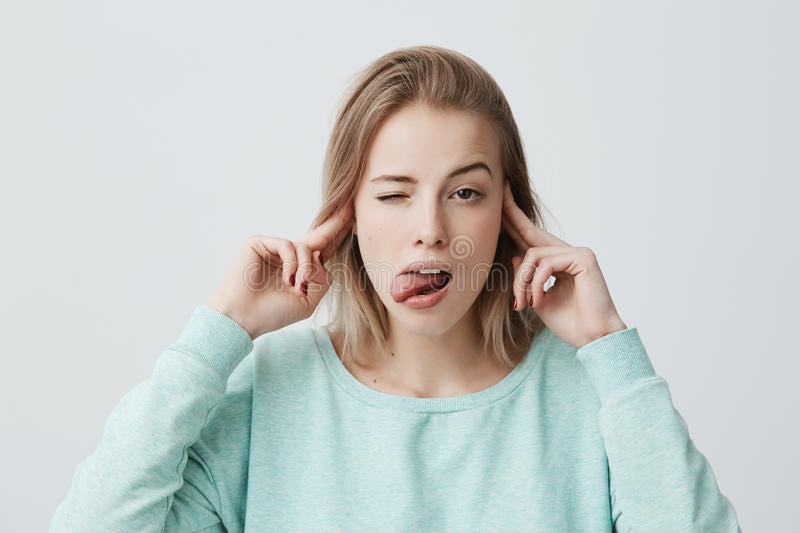 Studio portrait of bored and annoyed young blonde female frowning and plugging ears with fingers can`t stand noise. Or ignoring stressful unpleasant situation stock photo