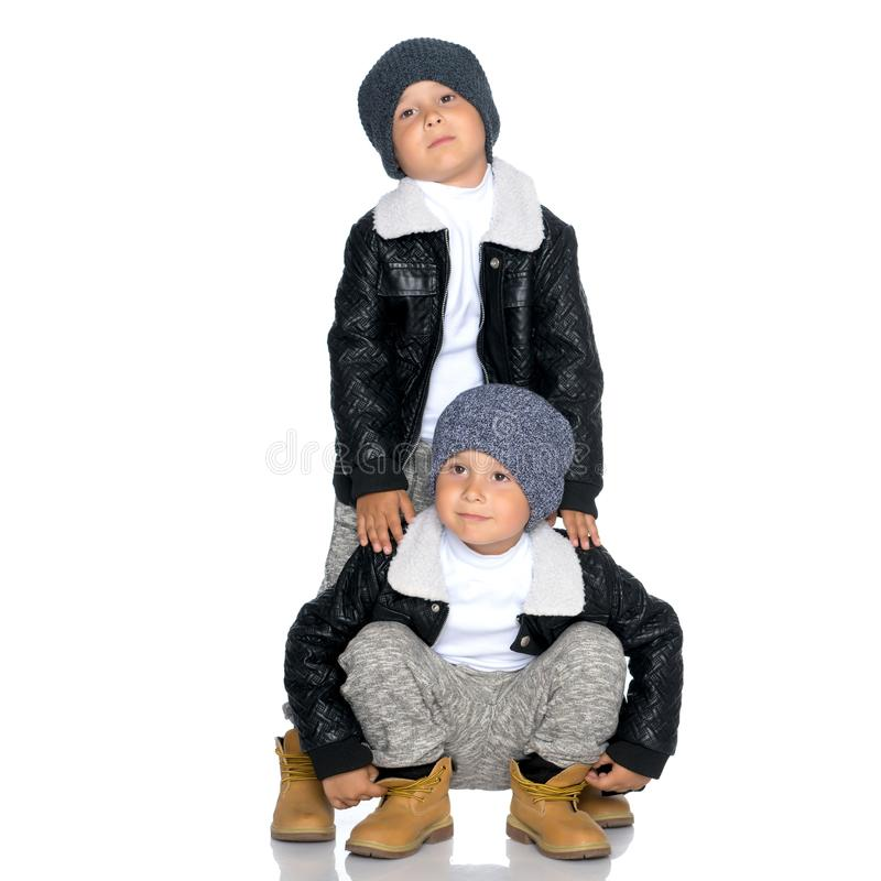 Two little boys in black jackets and hats. stock photography
