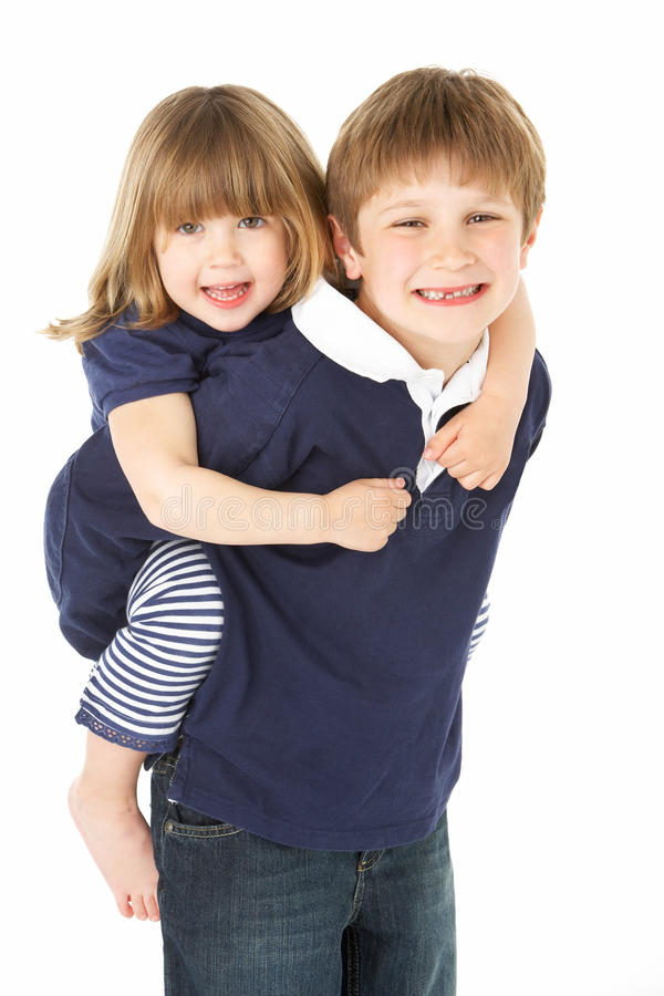 Studio Portrait Of Brother Giving Sister Piggy Back stock photo