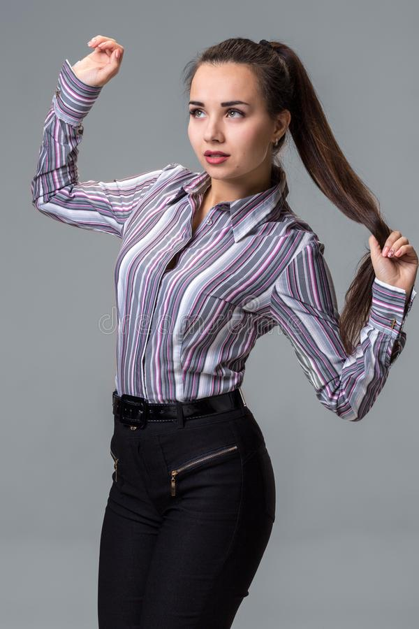 Studio portrait of brunette girl in striped shirt, trousers and long tail posing against grey background. stock photography