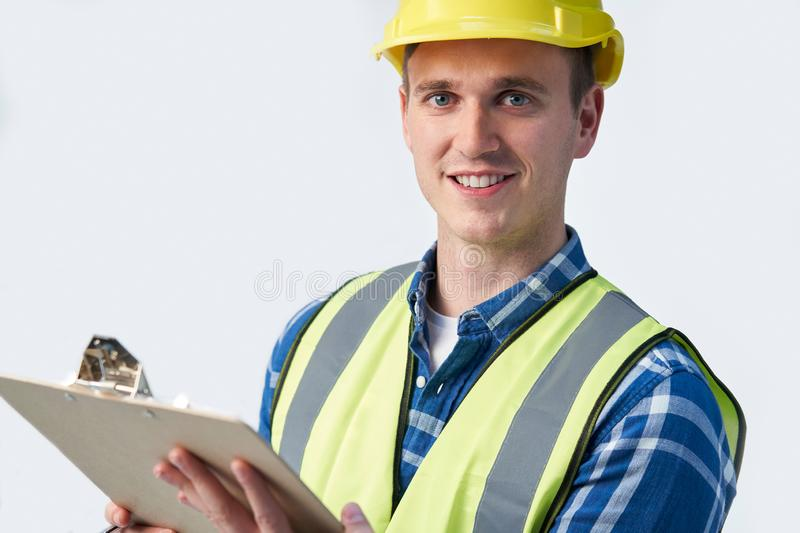 Studio Portrait Of Builder Architect With Clipboard Against White Background stock image