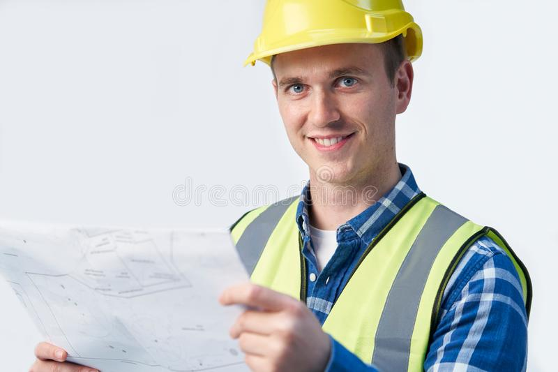 Studio Portrait Of Builder Architect Looking At Plans Against White Background royalty free stock photography