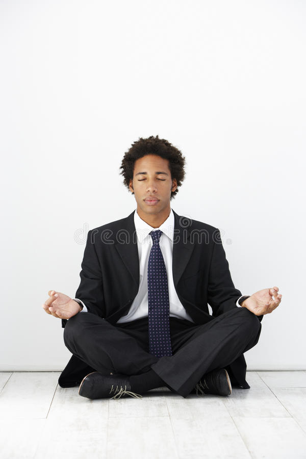 Studio Portrait Of Businessman Sitting On Floor Meditating stock photo