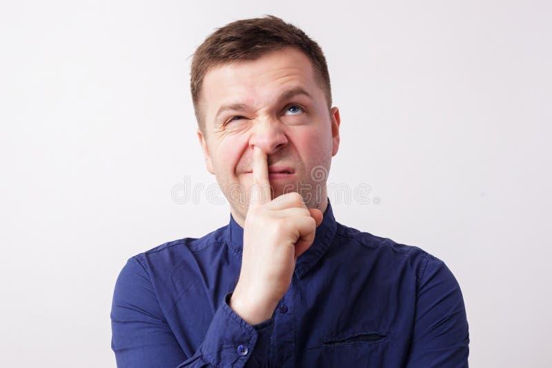 Studio portrait caucasian man finger in nose stock photo