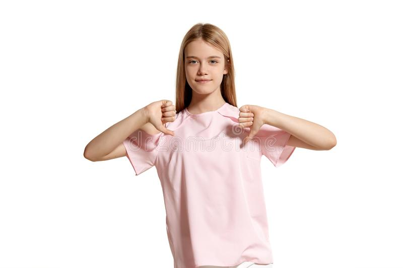 Studio portrait of a beautiful girl blonde teenager in a pink t-shirt posing isolated on white background. royalty free stock photo