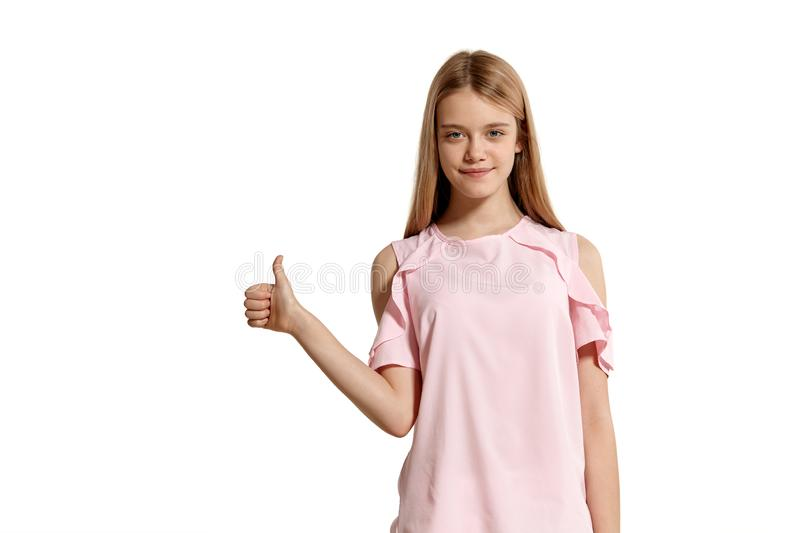 Studio portrait of a beautiful girl blonde teenager in a pink t-shirt posing isolated on white background. royalty free stock images