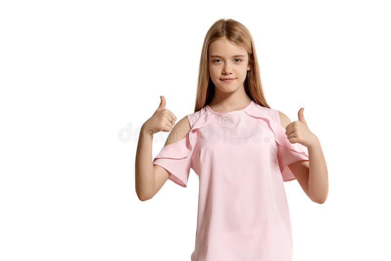 Studio portrait of a beautiful girl blonde teenager in a pink t-shirt posing isolated on white background. stock photography
