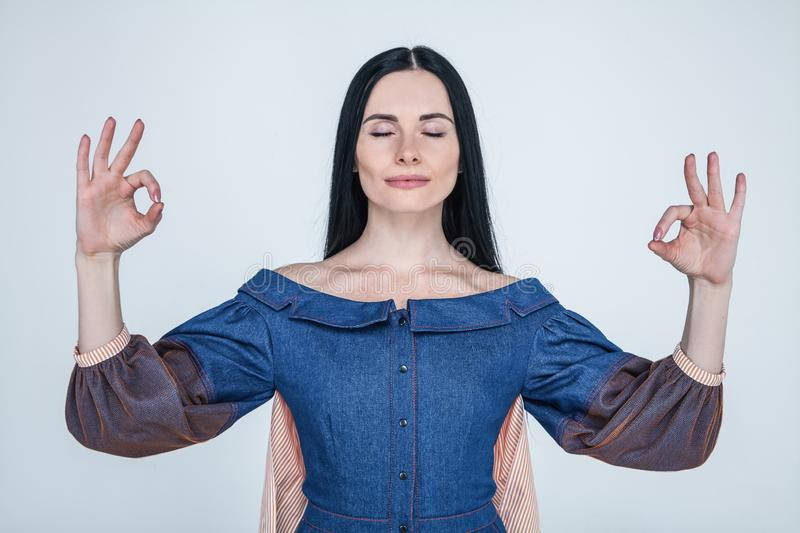 Studio portrait of charming positive caucasian female businesswoman trying to relax while meditating, standing with lifted hands stock photography