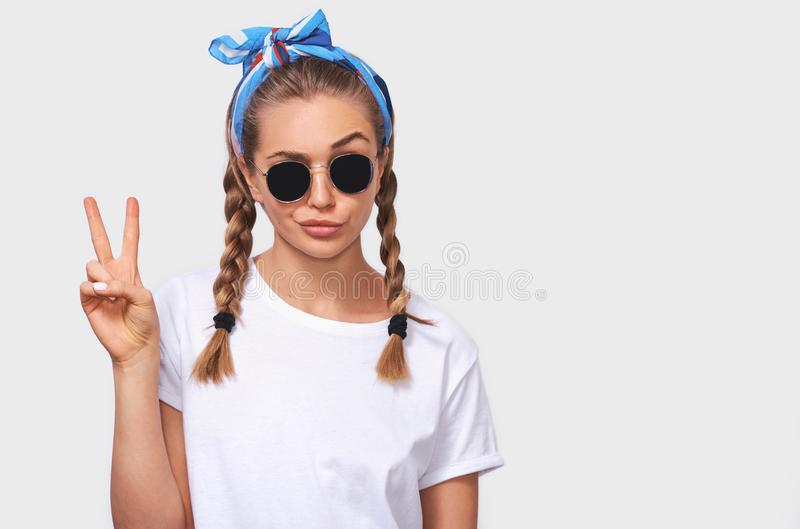 Cheerful blonde young woman wearing trendy sunglasses, white t-shirt and blue headband, making a duck face and showing peace sign. Studio portrait of cheerful stock photos