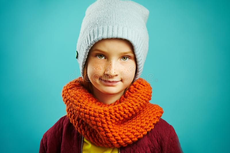 Studio portrait of child girl wearing a round scarf orange, blue winter hat, has beautiful face. Winter assortment of stock photos
