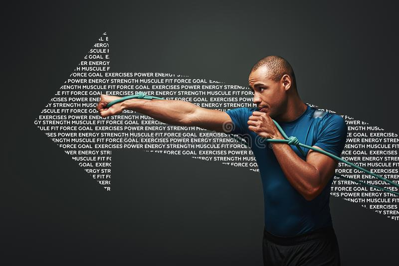 Full of energy. Sportsman working out with resistance band over dark background. Graphic drawing. Studio portrait of clean shaven young dark skinned male stock photo