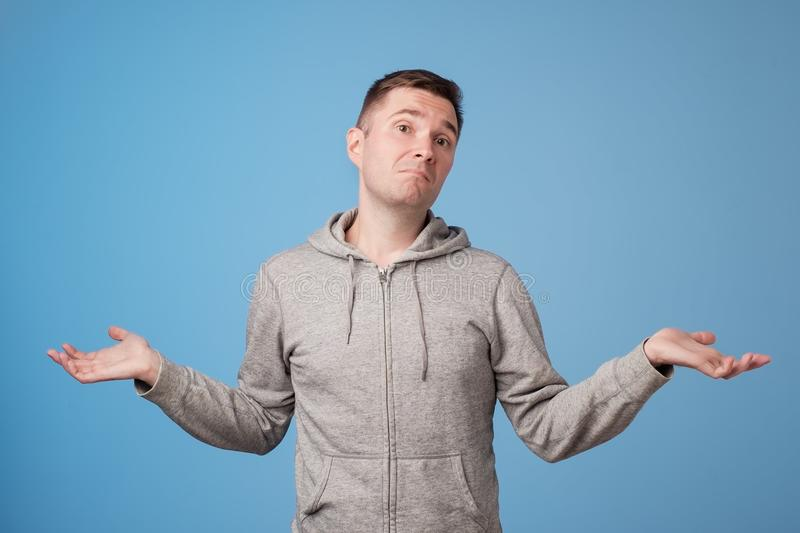 Studio portrait of confused handsome guy showing I have no idea gesture. stock photography