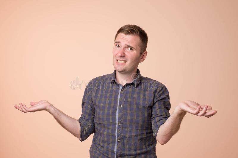 Studio portrait of confused handsome guy showing I have no idea gesture. royalty free stock photography