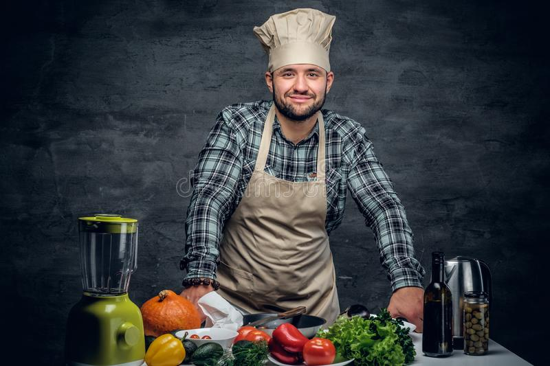 A cook man with fresh vegetables on a table. Studio portrait of a cook man with fresh vegetables on a table royalty free stock images