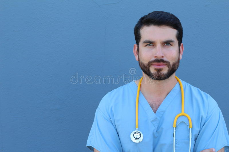 Studio Portrait Of Doctor Leaning Against Blue Background stock photo