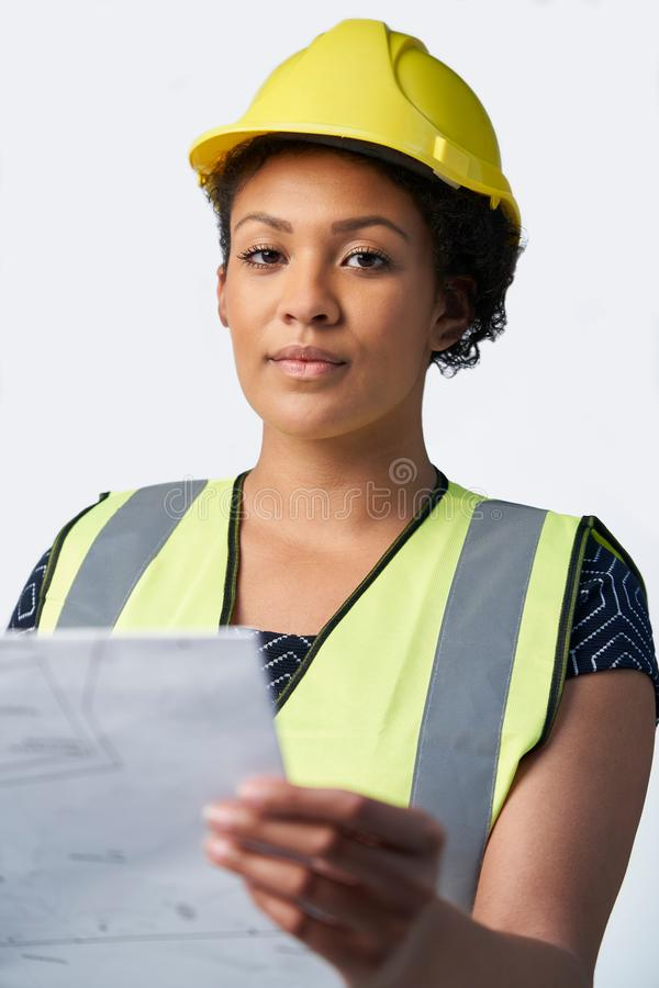 Studio Portrait Of Female Architect With Studying Plans Against White Background stock images