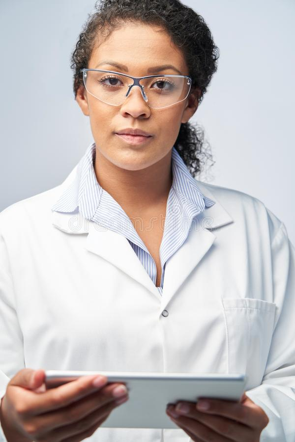 Studio Portrait Of Female Laboratory Technician Working With Digital Tablet royalty free stock image