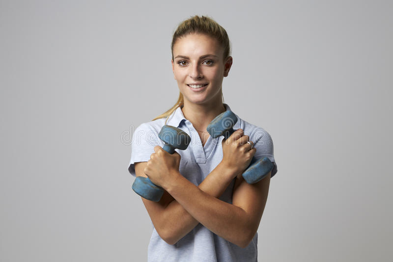 Studio Portrait Of Female Sports Coach Holding Weights stock photography