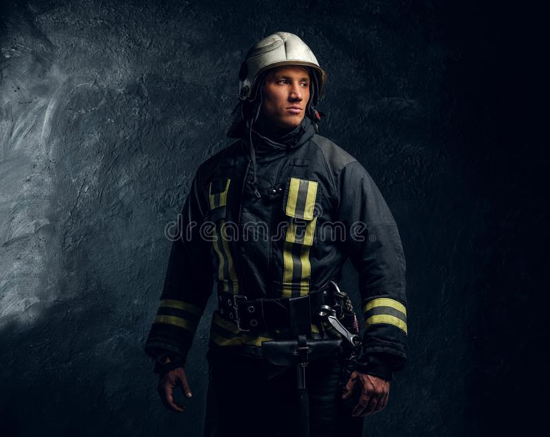 Portrait of firefighter dressed in uniform and safety helmet looking sideways with a confident look stock photography