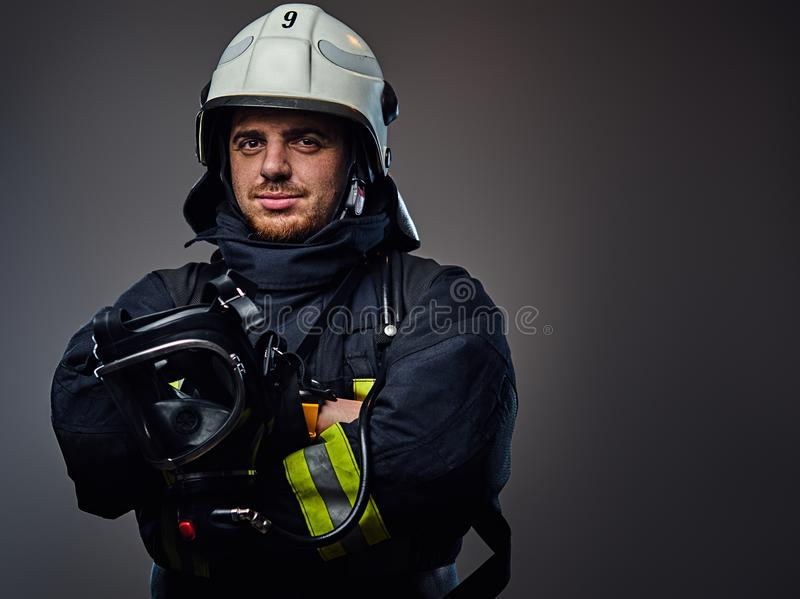 Studio portrait of firefighter dressed in uniform. royalty free stock photography