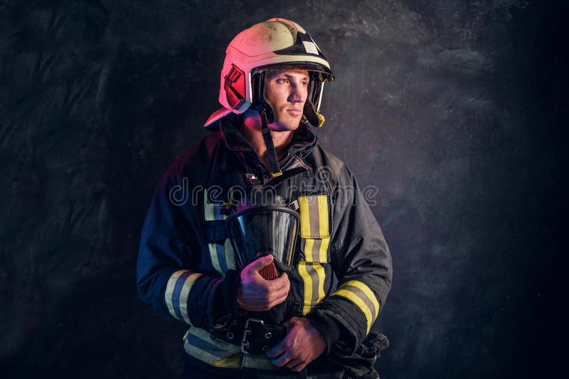 Portrait of a firefighter in uniform and safety helmet holding an oxygen mask and looking sideways with a confident look stock image