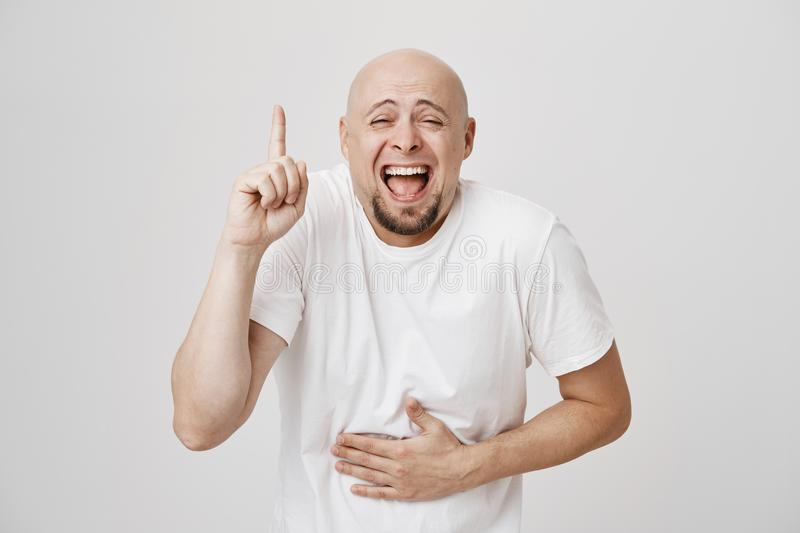 Studio portrait of funny bald bearded male bending towards camera while pointing up with index finger and laughing out. Loud, holding hand on belly, standing stock photography