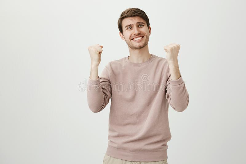 Studio portrait of funny emotive handsome man clasping raised fists and being excited because of victory or successful. Deal, standing over gray background stock image