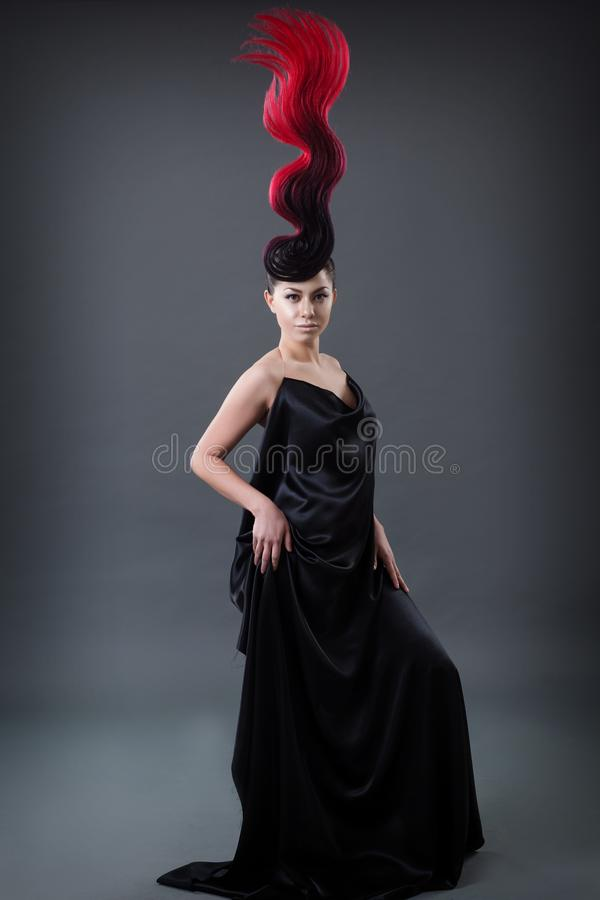 Studio portrait of a girl with a fiery hairdo royalty free stock photos