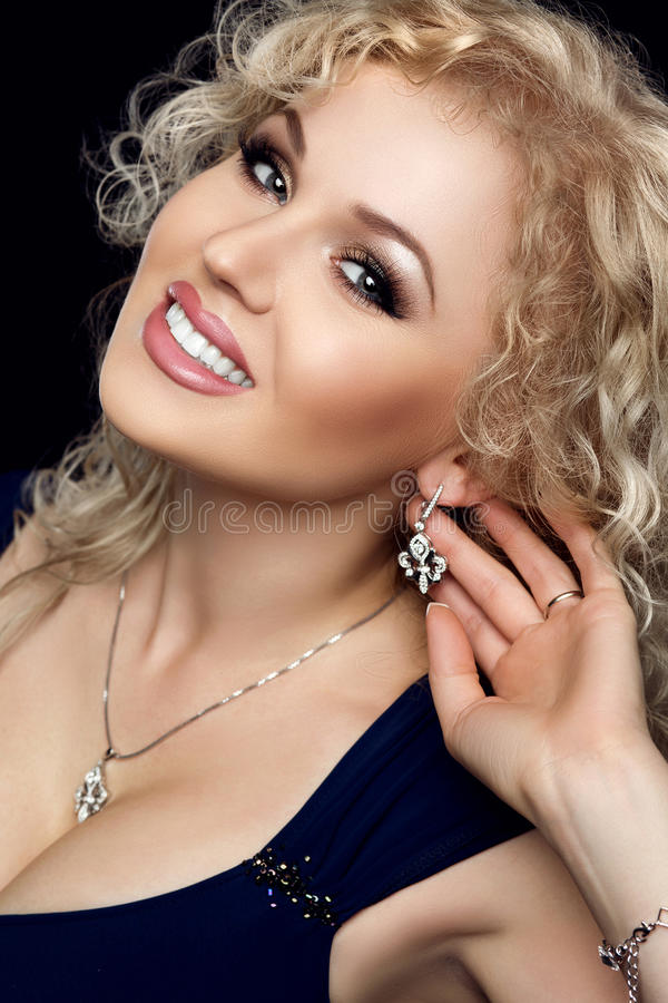 Studio portrait of gorgeous blonde woman smiling, darling necklace on her neck, earrings with precious stones touched by. The hand. Makeup gold, black hands stock photography