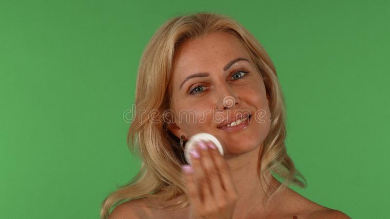 Attractive mature woman wiping her face with a cotton pad stock images