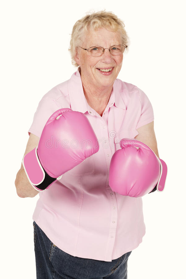 A studio portrait of a grandma wearing pink boxing gloves isolated on white. royalty free stock photography