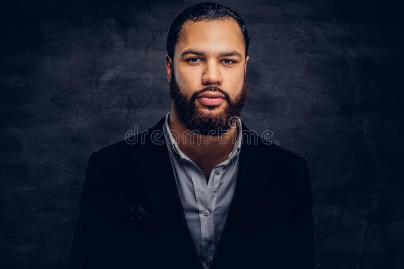 Studio portrait of handsome Afro-American male in an elegant black jacket and hat. stock images
