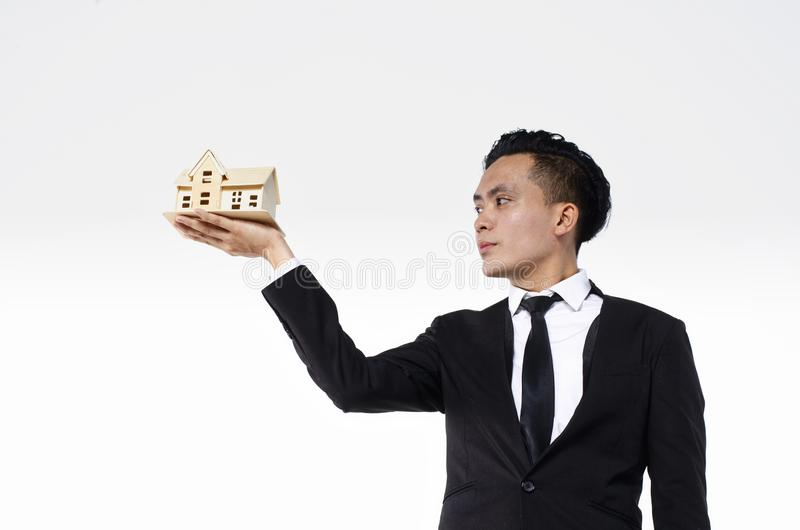 Confident young real estate agent on white background holding house model stock photos