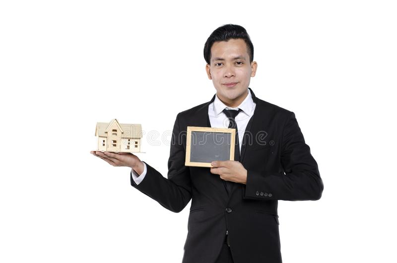 Young real estate agent on white background holding house model and signage for text royalty free stock photos