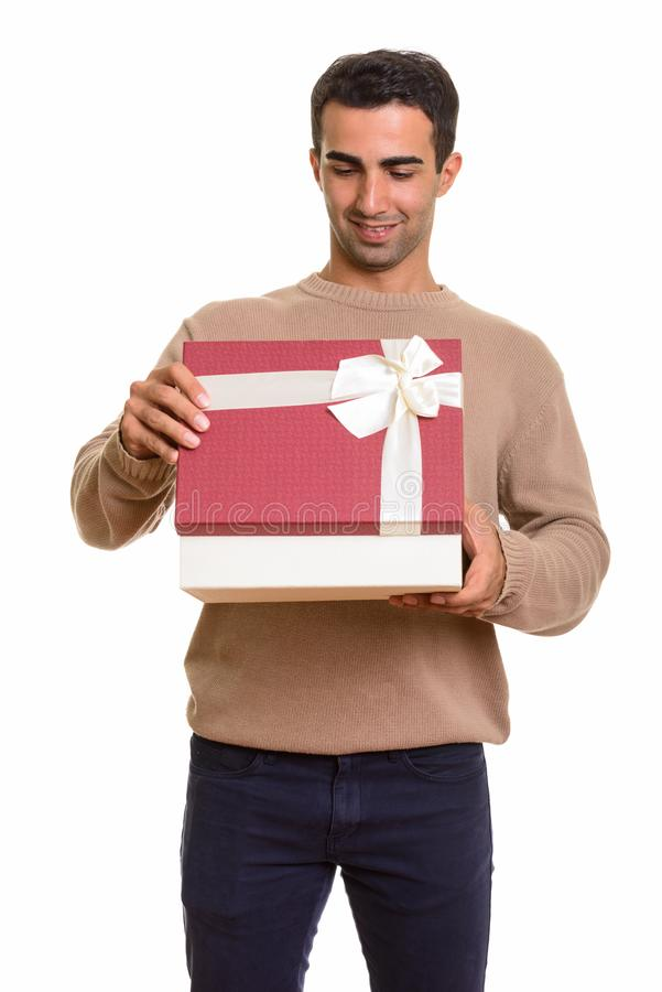Portrait of young handsome Persian man holding gift box. Studio portrait of handsome Iranian man isolated against white background royalty free stock image