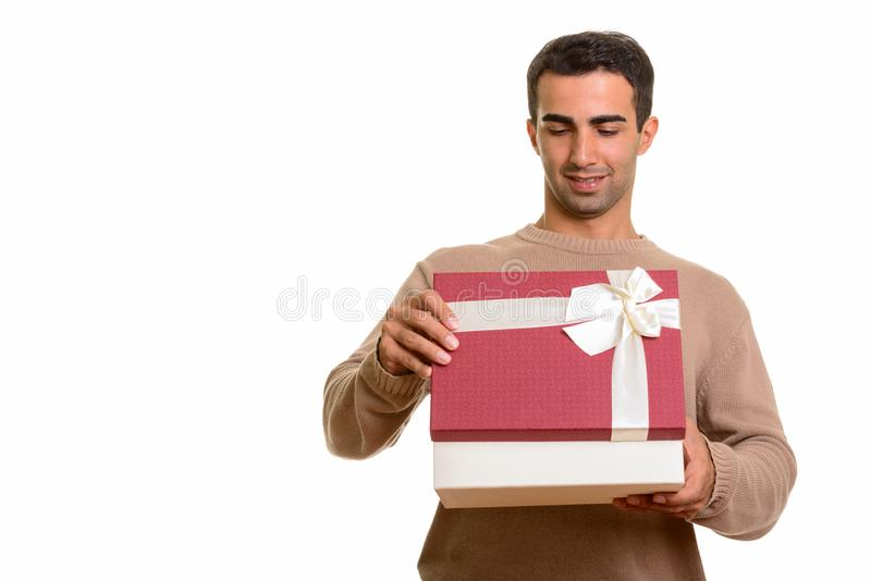 Portrait of young handsome Persian man holding gift box. Studio portrait of handsome Iranian man isolated against white background royalty free stock images