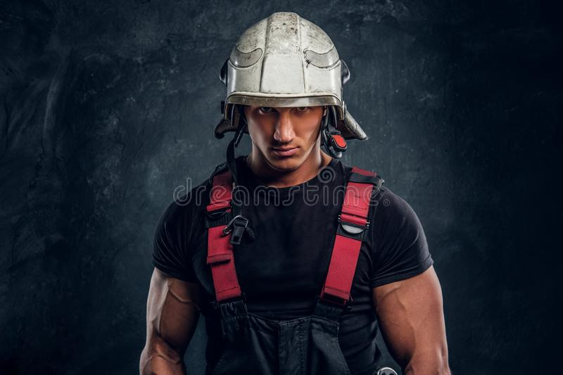 Portrait of a handsome man wearing a fire helmet and gloves, looking at a camera royalty free stock images