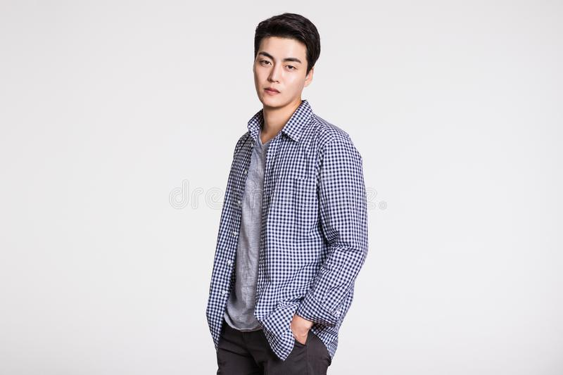 Studio portrait of a handsome young man posing confidently against a gray background royalty free stock photo