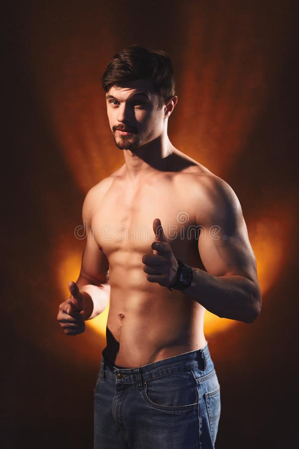 Smiling handsome man with muscular torso shows thumbs up sign stock images
