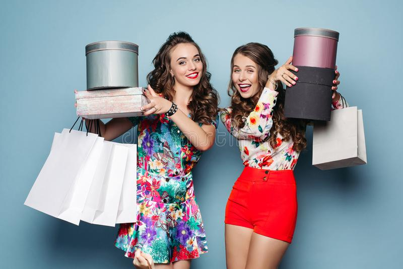 Smiling girlfriends in colorful clothes with many bags after shopping. stock images