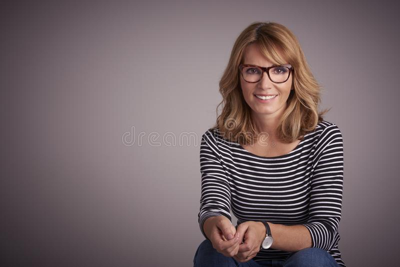 Mature woman sitting against at isolated grey background while looking at camera and laughing stock photography