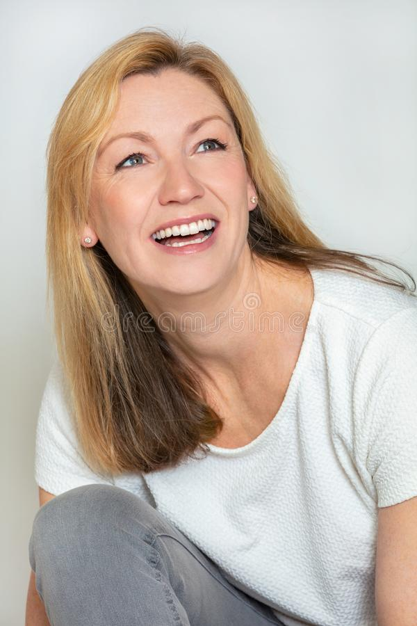 Studio portrait of an attractive happy middle aged blond woman in her forties royalty free stock image
