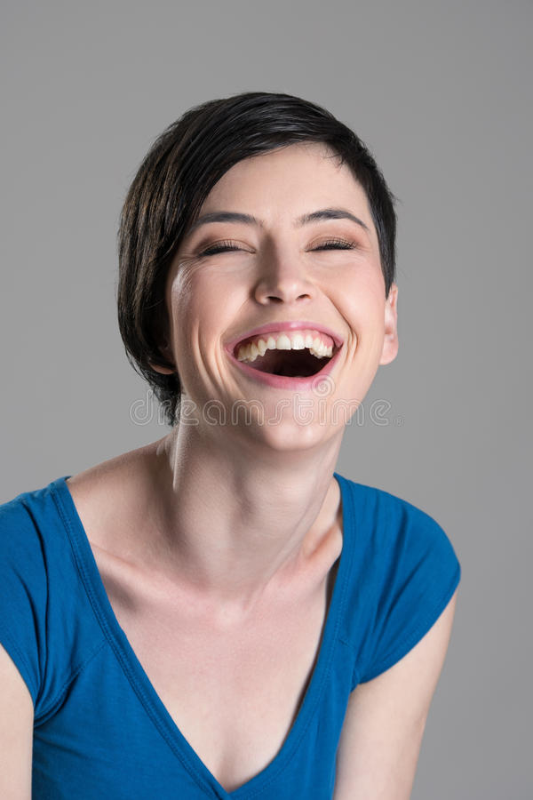 Studio portrait of heartily laughing young cheerful woman with open mouth royalty free stock photos