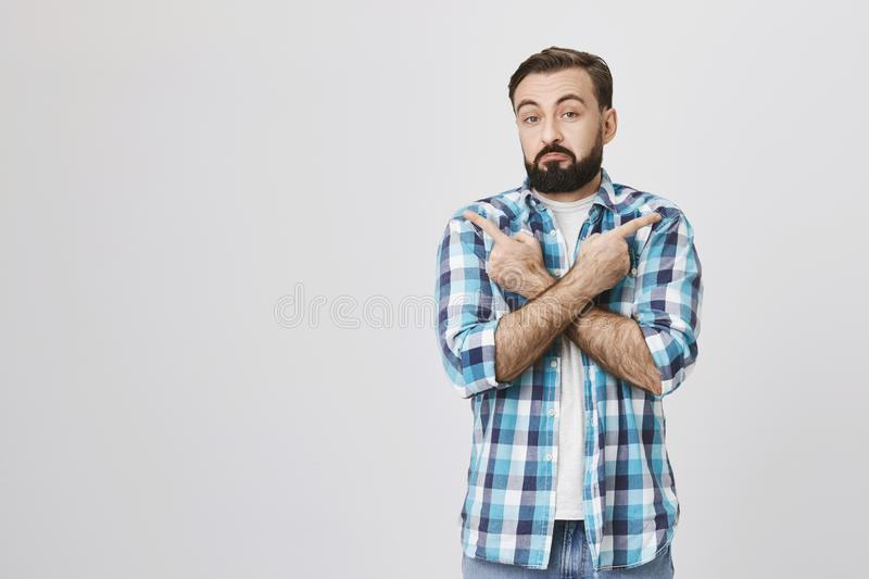 Studio portrait of interesting bearded man with gloomy smile and clueless expression, pointing in different directions stock photos