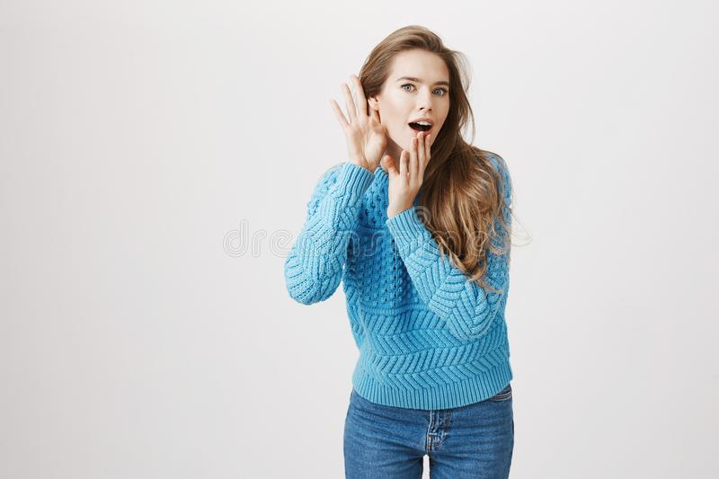 Studio portrait of intrigued european woman who likes to gossip, bending towards camera with hands near ear and opened. Mouth, being shocked with what she heard stock image