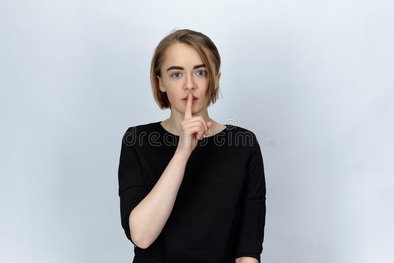 Studio portrait on isolated background of a young attractive woman with wide open eyes, holding a finger to call for silence royalty free stock images